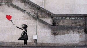 An image showing building art by artist Banksy depicting a little girl letting go of a heart balloon
