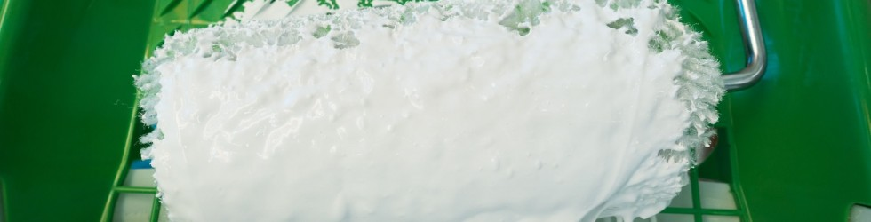 An image showing paint on a white roller being used by industrial painters