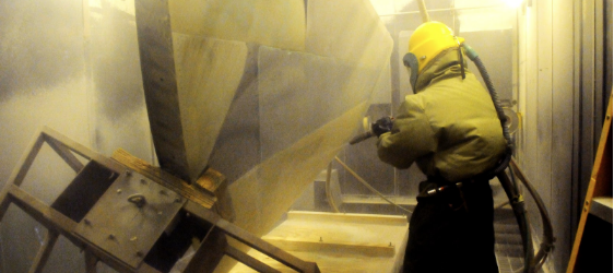an image of a worker in a blast room cleaning a metal part