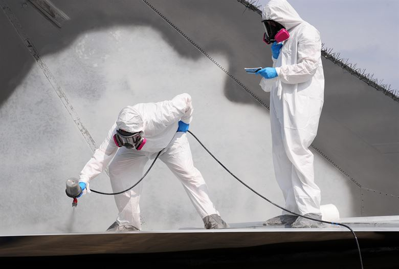 two operatives air spray painting a surface with a grey coating of paint