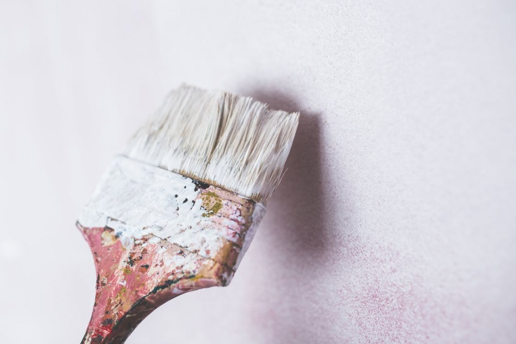a large paintbrush coating a wall with white paint
