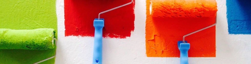 four paint rollers coating a while wall with different primary colours