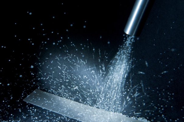 an image of shot blasting being used to clean a surface