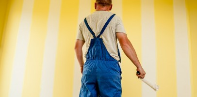 A professional painter stands in front of a yellow walll, painting the wall white in stripes, he is holding a paint roller