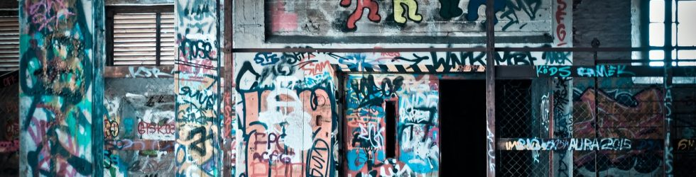 Image of an external wall of a building covered in graffiti. Outdoor graffiti can be removed using shot blasting methods.