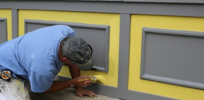 An image of a man painting the side of a building.